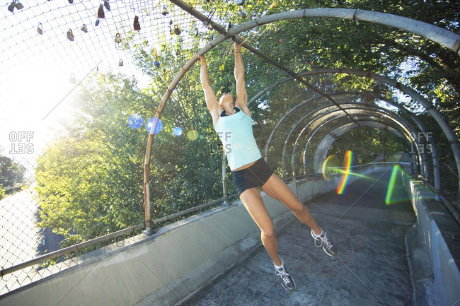 Sporty woman hanging from metallic arch over footpath at park