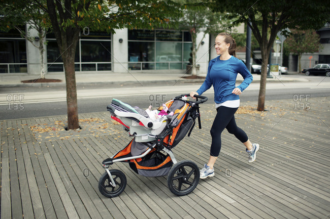 Cheerful woman looking at baby in while running on floorboard