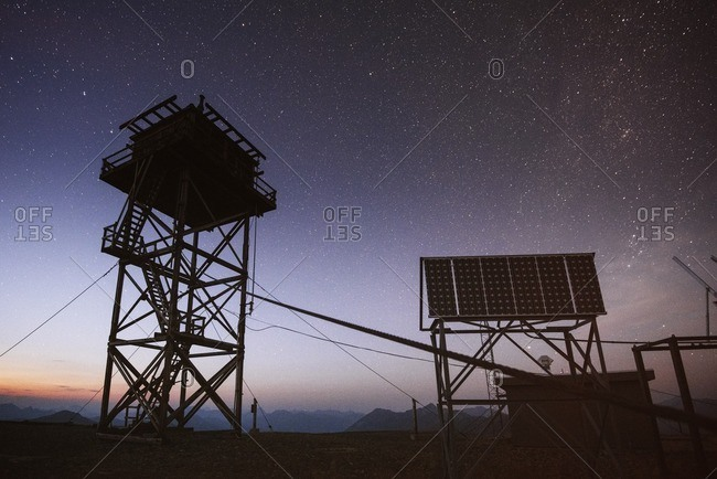Silhouette lookout tower and billboard against starry sky at night