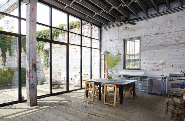 Table and chairs by large glass wall at home