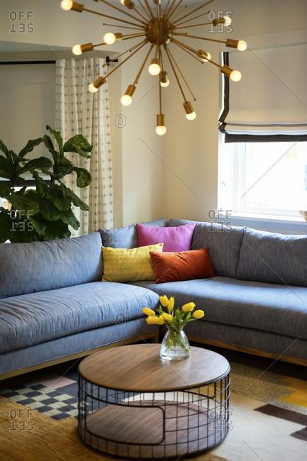 Modern pendant light hanging over sofa in living room