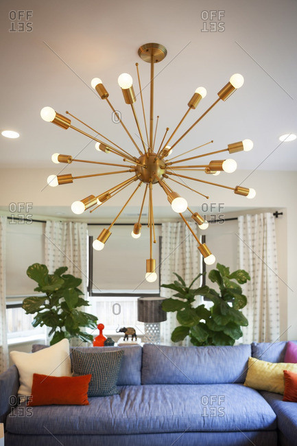 Illuminated pendant light hanging over couch in living room