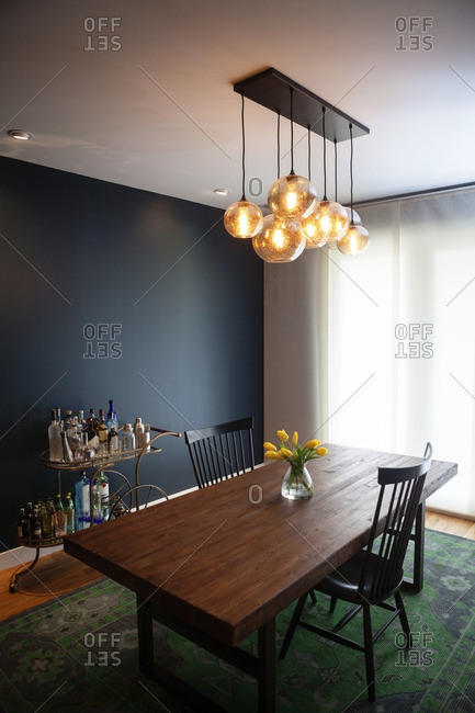 Illuminated pendant lights over dining table at home