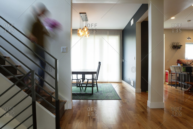 Blurred motion of woman moving down steps at home