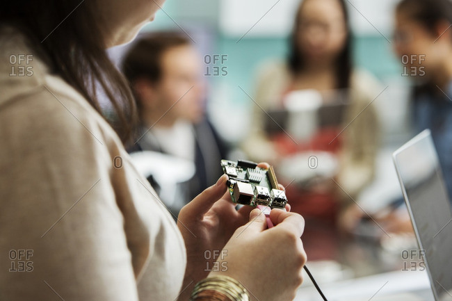 Cropped image of student attaching cable to circuit board with friends and teacher in background