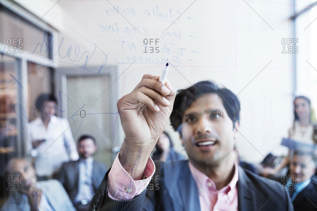 Businessman writing on glass wall and explaining during meeting in office
