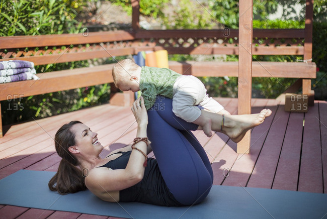 Cheerful woman playing with baby while lying on exercise mat