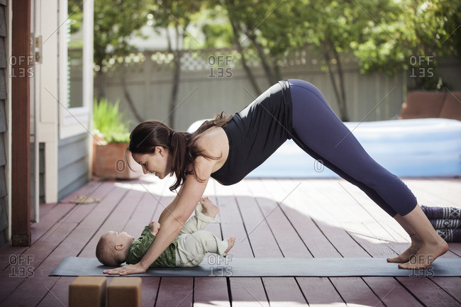Side view of woman practicing downward facing dog position while looking at baby in backyard