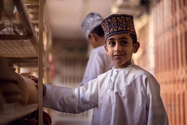 NIZWA, OMAN - APRIL 24 2015:Omani boy at the traditional market or souq in Nizwa, Oman.
