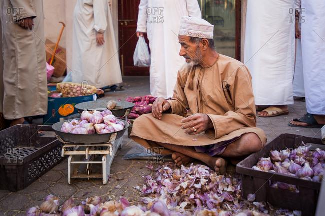 NIZWA, OMAN - APRIL 24 2015:Omani man selling garlic at the traditional market or souq in Nizwa, Oman