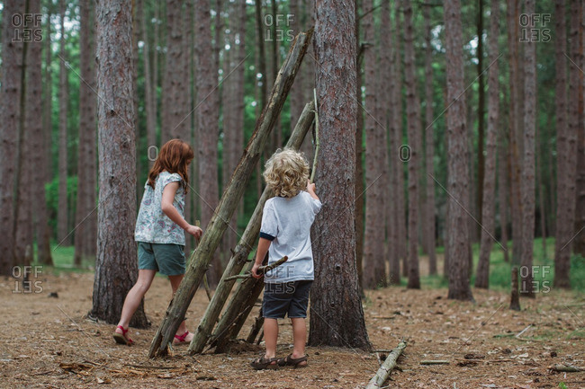 Kids propping logs against tree