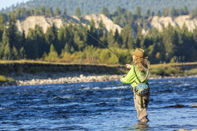Woman in waders fly fishing in river