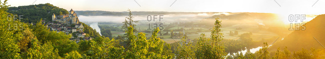 Early morning mist over the Dordogne River with Chateau de Castelnaud, Perigord, France
