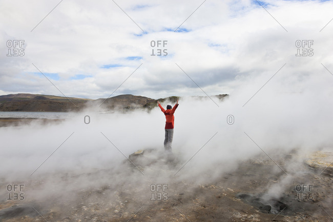 Woman standing on rock surrounded by the steam from geothermal pools, Iceland