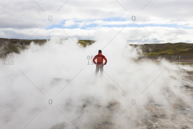 Hiker standing on rock surrounded by geothermal steam, Iceland