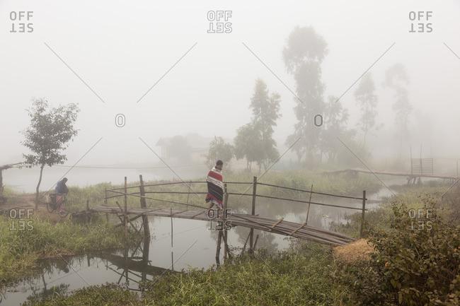12/9/12: Man walking across bridge in fog in rural India