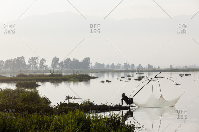 12/9/12: Silhouetted fisherman with net, India