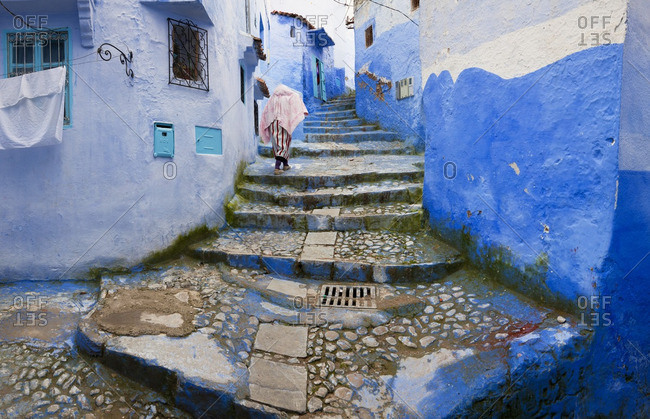 Person walking up stairs between blue buildings in Chefchaouen, Morocco