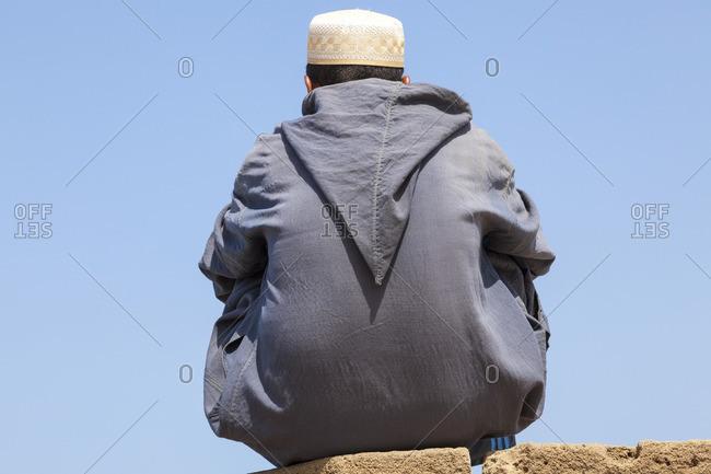 Man sitting on city walls in Essaouira, Morocco