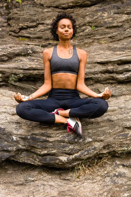 Woman sitting cross legged on rock meditating