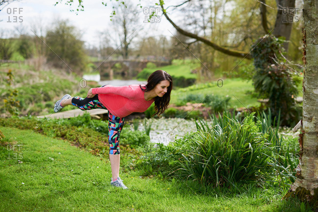 Pregnant woman outdoors, in yoga position