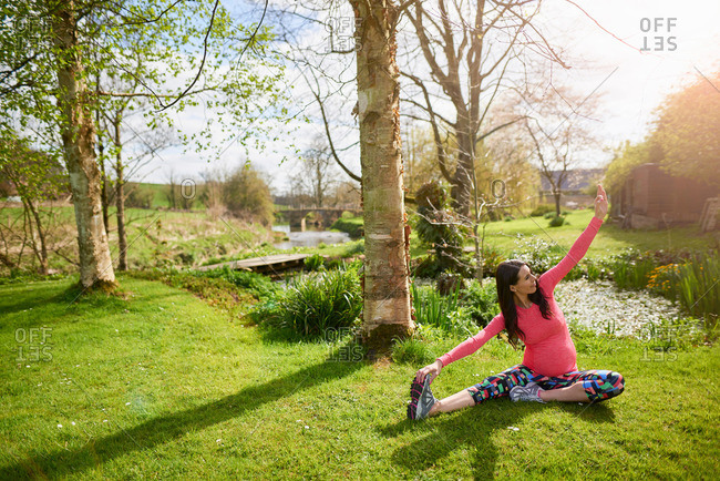 Pregnant woman stretching outdoors before exercising