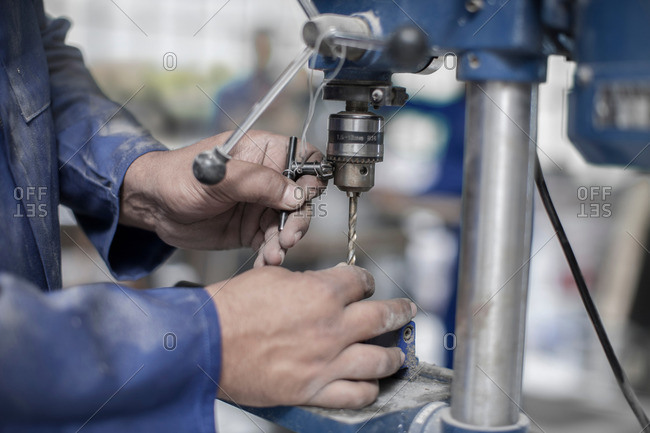 Close up of workers hands attaching drill bit in workshop