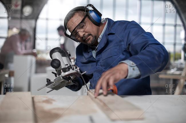 Carpenter using jigsaw tool in workshop