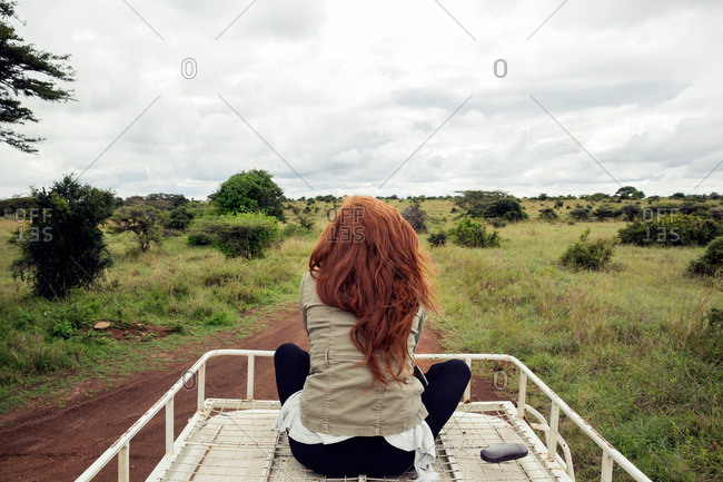 Woman riding on top of vehicle in wildlife park, Nairobi, Kenya