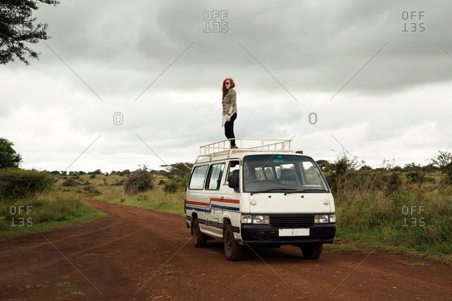 Nairobi, Kenya - April 16, 2016: Woman standing on top of vehicle in wildlife park