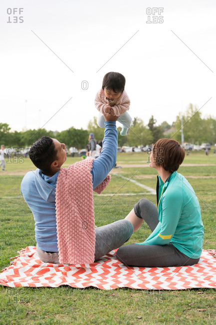 Couple playing with baby on blanket in park