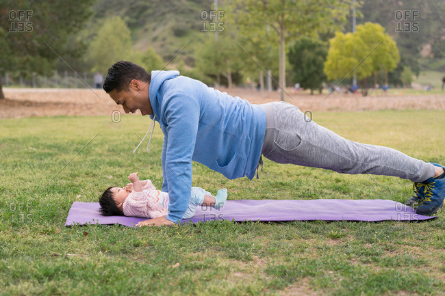 Father in plank pose over  baby in park