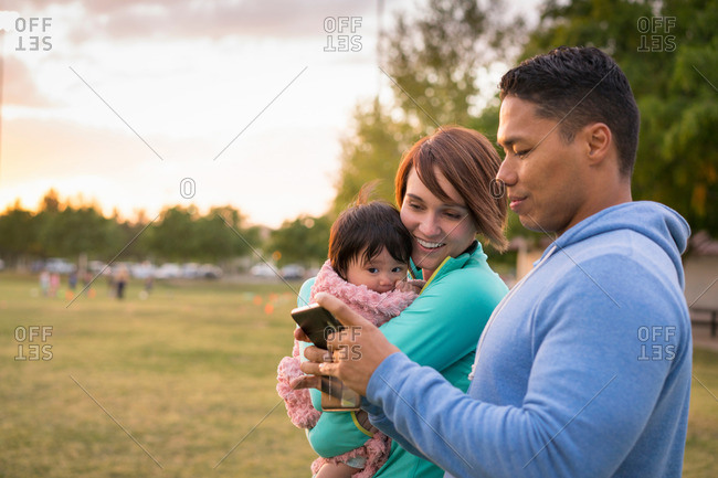Couple with baby, using mobile phone in park