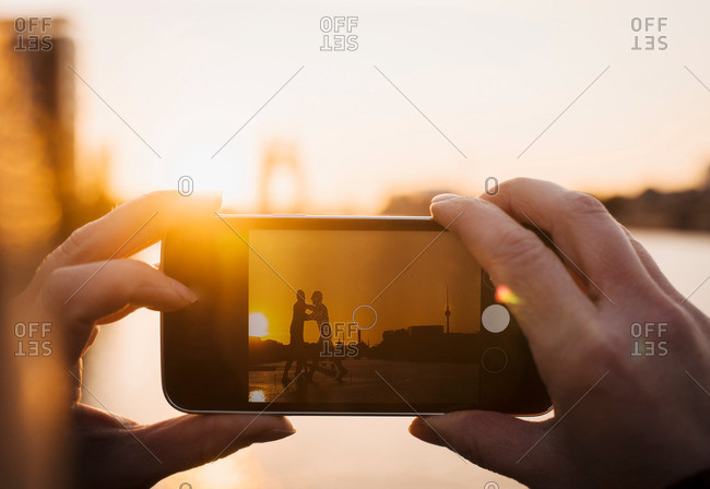 Person taking photograph of Molecule Man sculpture at sunset, Spree River, Berlin, Germany