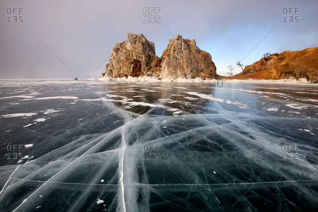 View of frozen ice and Shamanka Rock on Burkhan Cape, Baikal Lake, Olkhon Island, Siberia, Russia