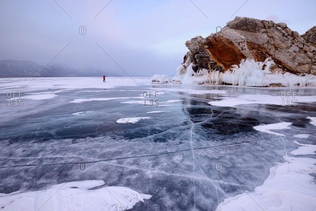Person on frozen ice by Borga-Dagan Island, Baikal Lake, Olkhon Island, Siberia, Russia