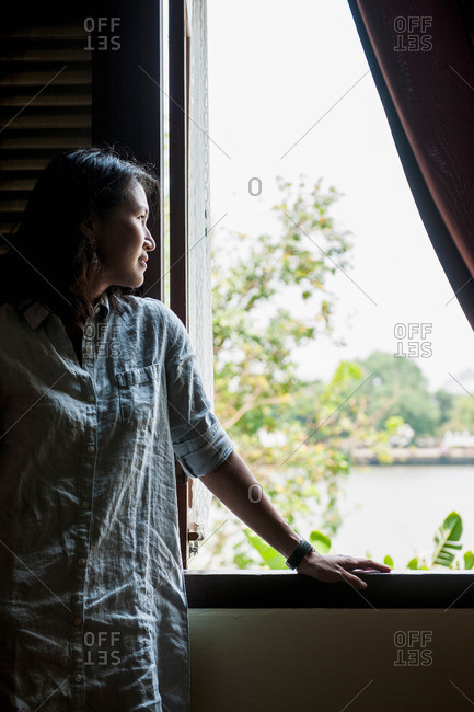 Woman looking out of a window to the Chao Phraya river in Bangkok, Thailand