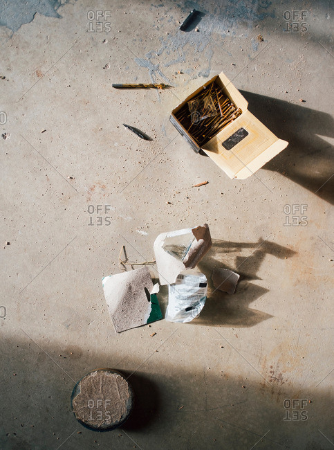Overhead view of a box of nails on a concrete floor
