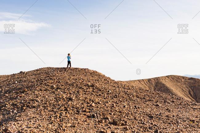 Boy on top of graveled hill in desert, Olancha, California, USA