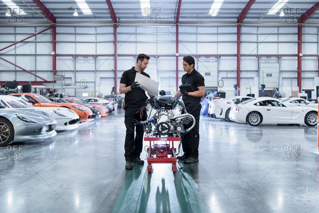 Garforth, UK - May 10, 2016: Engineers with engine for repair in racing car factory