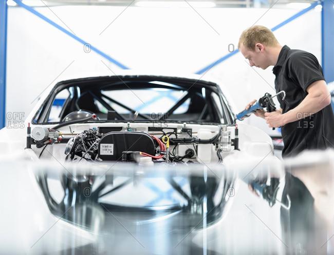 Engineer building car in racing car factory
