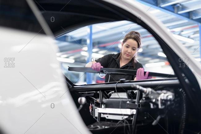 Female engineer assembles car - Offset