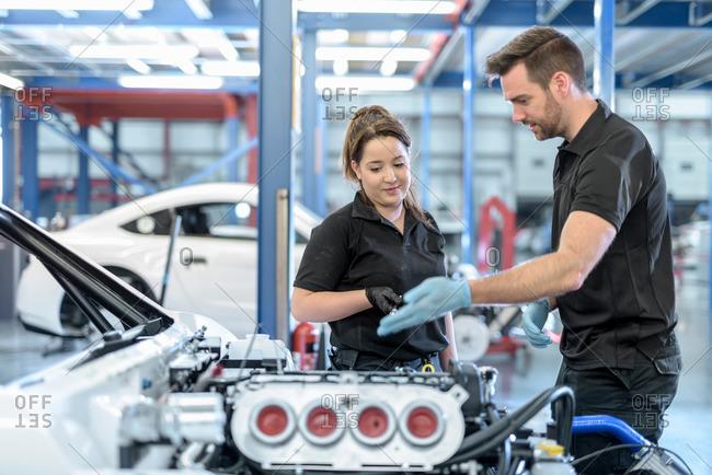 Engineers discuss car in racing car factory