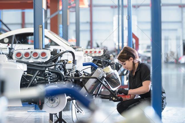 Female engineer assembles car in racing car factory