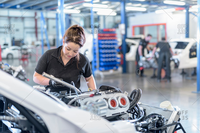 Female engineer assembles car in factory