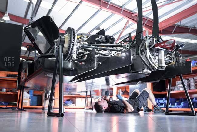 Engineer working underneath car in racing car factory