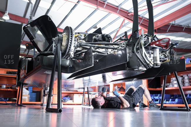 Engineer working underneath car in racing car factory