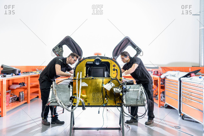 Engineers with car under construction in racing car factory