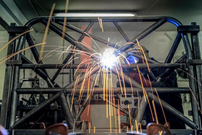 Man welding rollcage in racing car factory