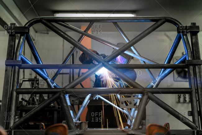Welder welding rollcage in racing car factory